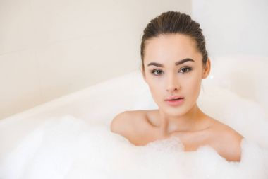 portrait of attractive young woman taking bath with foam at home