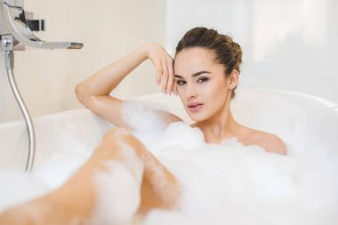 attractive young woman taking bath with foam at home