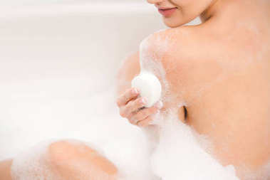 cropped shot of smiling woman with soap taking bath