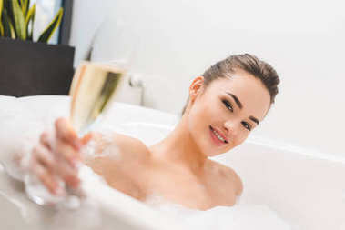 selective focus of beautiful woman with glass of champagne taking bath
