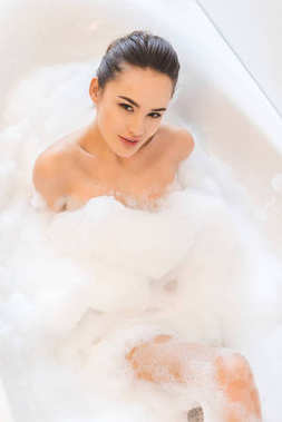 overhead view of beautiful young woman taking bath at home