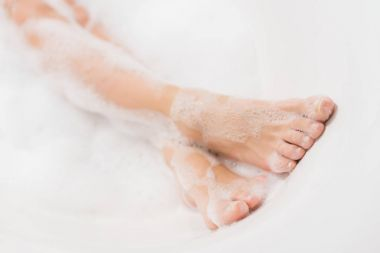 partial view of female legs in bath with foam
