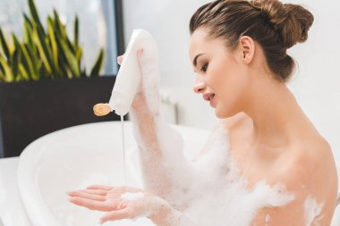 side view of young woman taking bath with gel and foam