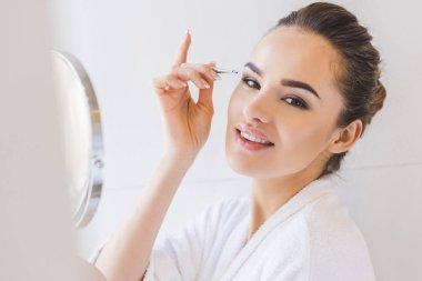 Young woman plucking eyebrows with tweezers stock vector