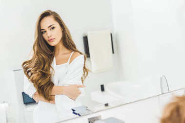 mirror reflection of attractive young woman in bathroom