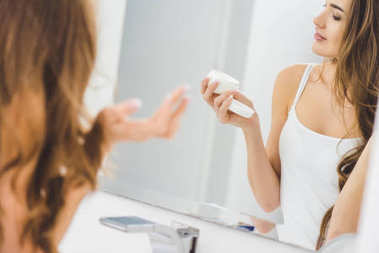 beautiful woman looking at face cream in hand