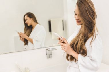 beautiful woman using smartphone in bathroom at home