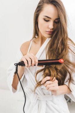 portrait of woman straightening hair with hair straightener