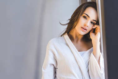 portrait of attractive young woman in bathrobe at home