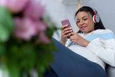 Fotografie africká americká těhotná žena poslech hudby se sluchátky a pomocí smartphone