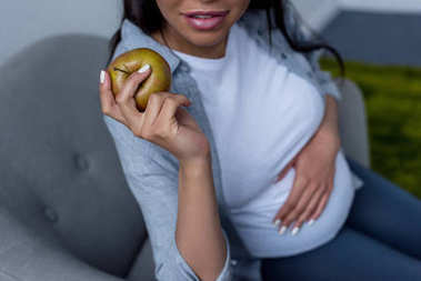cropped view of african american pregnant woman holding apple