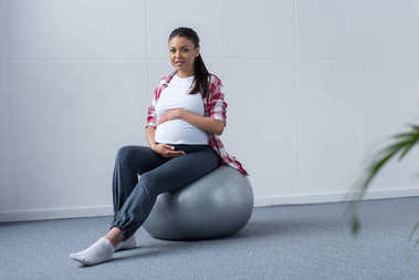 sportive african american pregnant woman sitting on fit ball