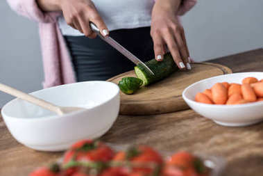 cropped view of woman cutting cucumber and making salad at kitchen