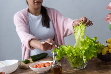 cropped view of african american pregnant woman making fresh salad at kitchen