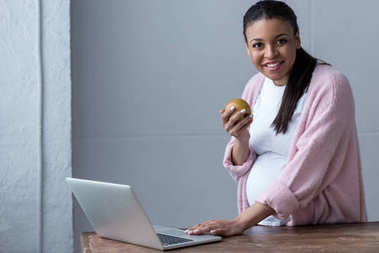 african american pregnant woman with apple using laptop