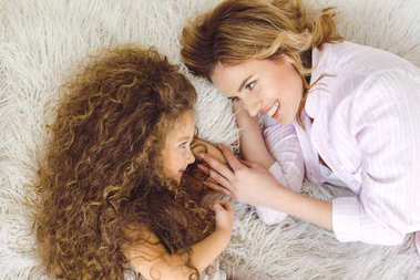 top view of happy mother and adorable curly daughter lying on sheep skin blanket