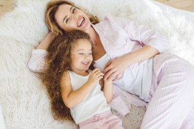 laughing mother and daughter lying on sheep skin blanket
