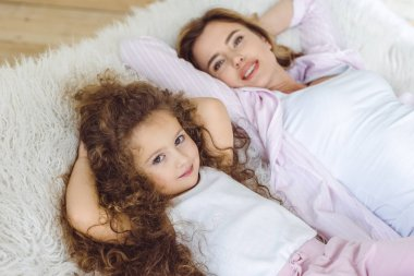happy daughter and beautiful mother lying on sheep skin blanket