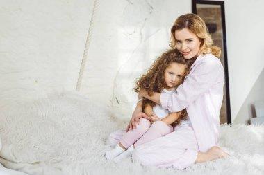 attractive mother hugging her upset little daughter on sheep skin blanket