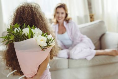 little daughter with bouquet of flowers for her mom on happy mothers day