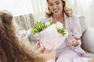 daughter presenting bouquet of flowers to her smiling mom on happy mothers day