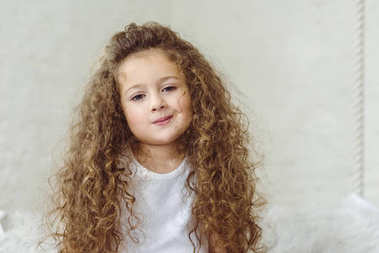 portrait of adorable curly child looking at camera