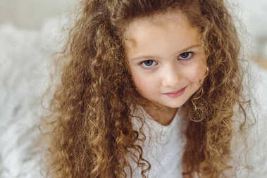 portrait of adorable curly kid looking at camera