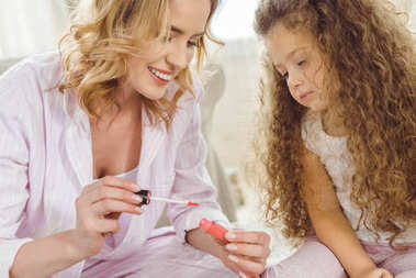 curly daughter and smiling mother with lip gloss