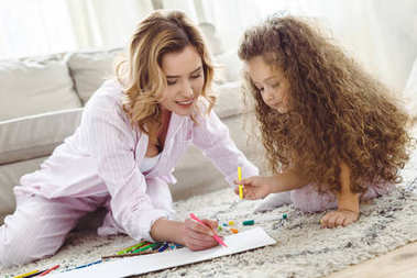 adorable daughter and mother drawing with markers in album together
