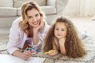 curly daughter and beautiful mother with markers and drawing album looking at camera