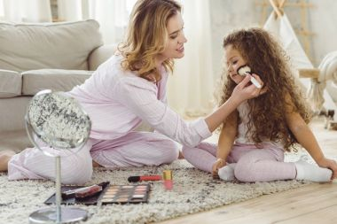 mother applying face powder to her daughter