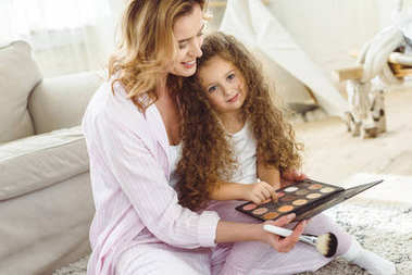 mother teaching her daughter to apply makeup
