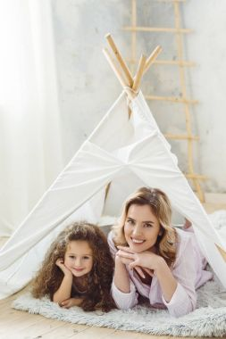 beautiful cheerful mother and curly daughter lying in kid wigwam