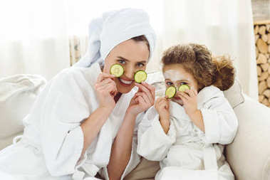 happy mother and daughter with cucumber slices doing cosmetic procedures
