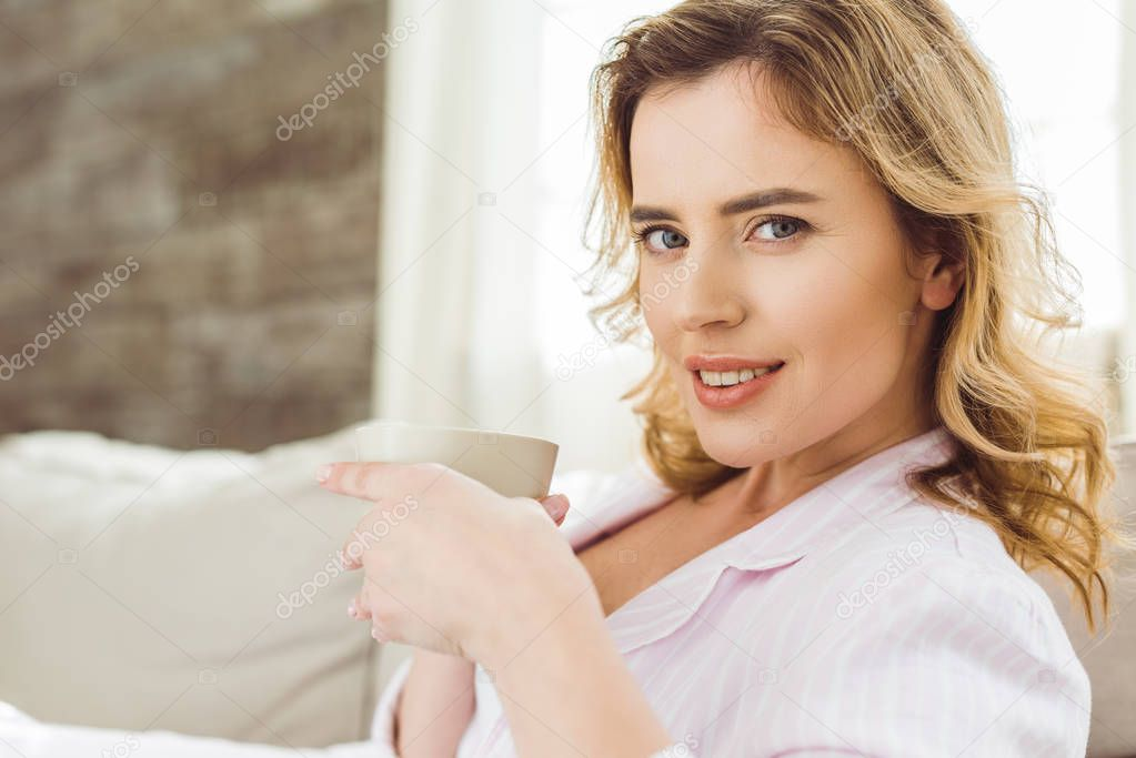 portrait of woman holding cup of coffee while sitting on sofa