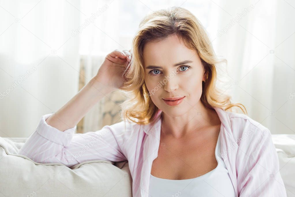 blonde woman in pajamas sitting on sofa at home