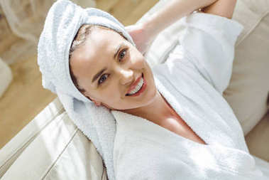 attractive smiling woman relaxing with towel on head