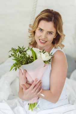 smiling blonde woman with bouquet of flowers for 8 march