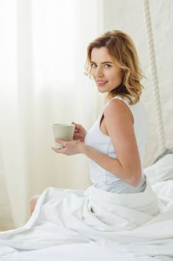 Smiling beautiful woman with cup of coffee sitting on bed in the morning stock vector