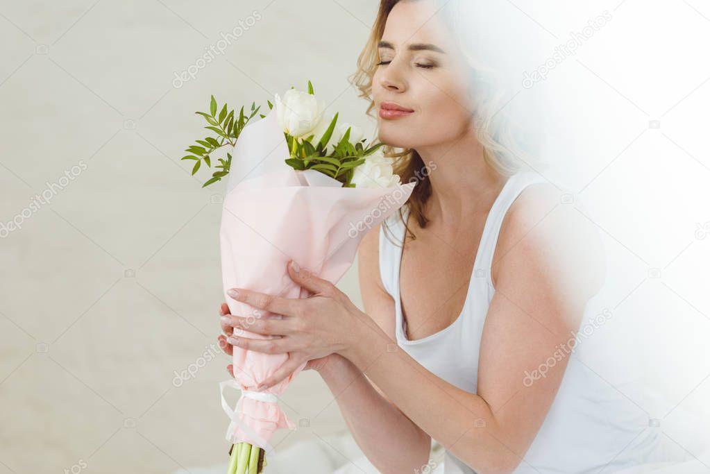 beautiful woman sniffing bouquet of flowers for international womens day
