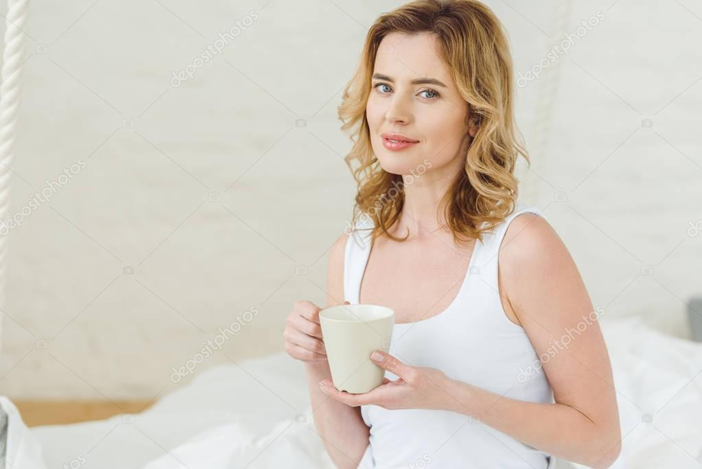 smiling blonde woman with cup of coffee in bedroom in the morning