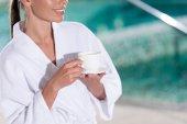 abgeschnittene Aufnahme eines lächelnden Mädchens im Bademantel mit einer Tasse Kaffee im Kurzentrum