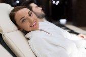šťastná mladá žena se usmívá na kameru při odpočinku v lázeňském centru