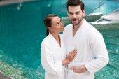 mladý pár v župany stojící poblíž bazén v lázeňském centru