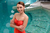 Fotografie atraktivní mladá žena v plavky stojí s překřížením rukou a usmívá se na kameru v lázeňském centru