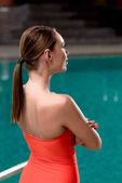 Fotografie zadní pohled na dívku v červené plavky stojící poblíž bazén v lázeňském centru