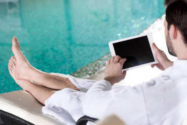 cropped shot of man in bathrobe using digital tablet with blank screen