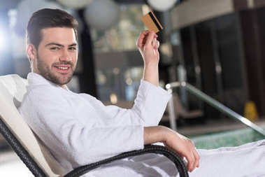 young man in bathrobe holding credit card and smiling at camera in spa center