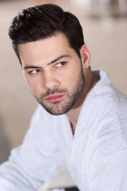 handsome bearded young man in bathrobe looking away