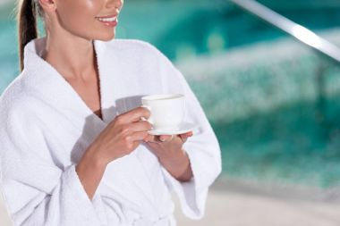 cropped shot of smiling girl in bathrobe holding cup of coffee in spa center